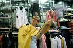 Shopping. Happy pregnant female posing in shop with yellow jacket Royalty Free Stock Images