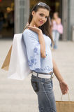 Shopping. Beautiful brunette standing in front of a shop with bags and sun glasses Stock Images