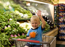 Shopping. Image of little boy in shopping cart holding bell paper stock image
