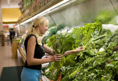 Shopping. Young woman picking vegetables in the store stock images