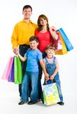 After shopping. Portrait of happy family standing and holding bags while looking at camera with smiles