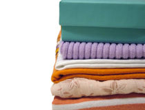 Shopping. Stack of cloths and a gift box on white background stock photography