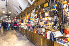 Shopping arcade in the Sukiennice cloth hall in Krakow. KRAKOW, POLAND - MAY 4: people in Passage with artistic craft souvenir stalls of the gothic cloth hall Royalty Free Stock Image