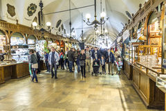 Shopping arcade in the Sukiennice cloth hall in Krakow. KRAKOW, POLAND - MAY 4: people in Passage with artistic craft souvenir stalls of the gothic cloth hall Stock Photos