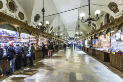 Shopping arcade in the Sukiennice cloth hall in Krakow. KRAKOW, POLAND - MAY 4: people in Passage with artistic craft souvenir stalls of the gothic cloth hall Stock Photography