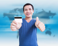 Shopping Around The World. Asian Man With Credit Card And Showing Thumb Up Royalty Free Stock Photography