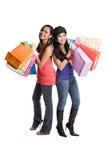 Shopping asian women. An isolated shot of two beautiful asian women carrying shopping bags Stock Images