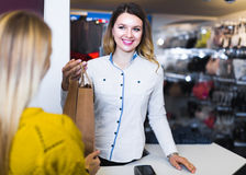 Shopping assistant handing purchases to woman in underwear store. Female shopping assistant handing purchases to women in underwear store Royalty Free Stock Photography