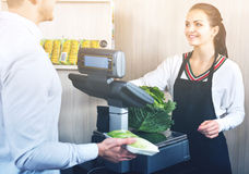 Shopping assistant helping customer to weigh cabbage Royalty Free Stock Photos