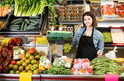 Shopping assistant weighing fruit and vegetables in grocery shop. Young european shopping assistant weighing fruit and vegetables in grocery shop Royalty Free Stock Photo