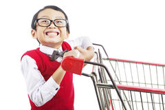 Shopping for back to school. Smiling elementary school student with shopping cart. shot in studio isolated on white Stock Photo
