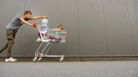 Shopping background. Happy father with kids inside the shopping cart, trolley pushing the cart ahead. Shopping with