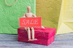Shopping background with wooden dummy. Wooden mannequin sitting on gift box and holding red card with inscription sale stock photo