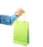 Shopping Bag. A hand of a man in blue shirt holding a green shopping bag, isolated on a white background Stock Photo