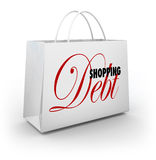 Shopping Bag Debt Compulsive Spending Broke. Shopping Debt words on a bag illustrating spending too much money on goods and merchandise at a retail store and Royalty Free Stock Photos