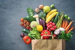 Shopping bag full of fresh vegetables and fruits stock images
