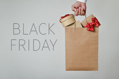 Shopping bag full of gifts and text black friday. Closeup of a young caucasian man with a paper shopping bag full of gifts in his hand and the text black friday Stock Images