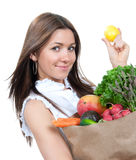 Shopping bag full of groceries. Happy young woman holding a paper shopping bag full of groceries, mango, salad, asparagus, radish, avocado, carrots and lemon in Royalty Free Stock Photography