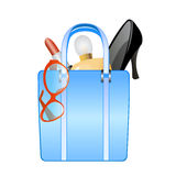 Shopping bag full of products. Isolated shopping bag with female products as sun glasses, shoes, lipstick and perfume Royalty Free Stock Photo