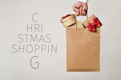 Shopping bag with gifts and text christmas shopping Stock Photos