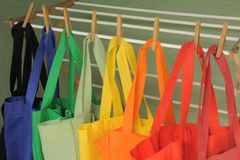 Shopping Bag Laundry. Rainbow of reusable shopping bags drying on a clothes rack Royalty Free Stock Photography