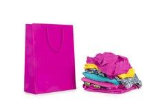 Shopping bag and a pile of clothes Stock Photos