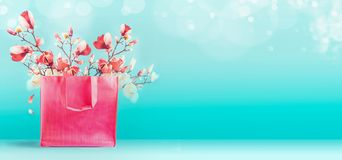 Shopping bag with pink spring blossom bunch standing at turquoise blue background. Trendy color. Creative spring time and summer. Concept. Magnolia blooming stock photography
