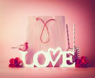 Shopping bag with red stripes , word LOVE and decoration tools at red pink background, front view. Copy space Stock Photo