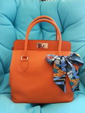 Shopping bag toolbox orange bag hermes scarf silkscarf twilly. Hermes toolbox in orange with blue twilly Royalty Free Stock Photos