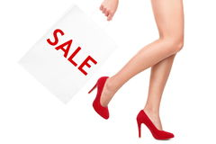 Shopping bag woman - sale. Sign. Closeup of woman legs and shopping bags saying sale. Isolated on white background Royalty Free Stock Image