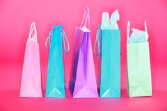 Shopping bags. On pink background. Many colorful shopping paper bags standing on pink floor royalty free stock images