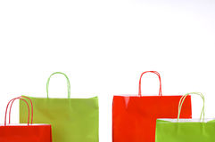 Shopping bags. Festive red and green Christmas shopping bags isolated against white background royalty free stock photography
