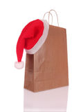 Shopping bags. Paper shopping bags with a Christmas hat on white background Royalty Free Stock Photos