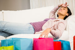 Shopping bags against brunette lying on sofa Royalty Free Stock Photos