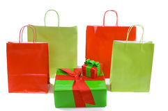 Shopping bags and Christmas gifts. Festive red and green Christmas shopping bags and Christmas gifts isolated against white background stock photo
