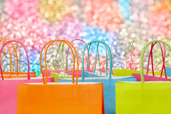 Shopping bags. Colorful paper shopping bags against glitter background Royalty Free Stock Photography