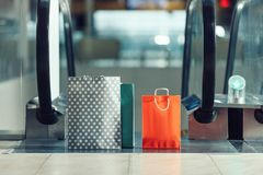 Shopping bags in front of escalator at shopping mall stock photo