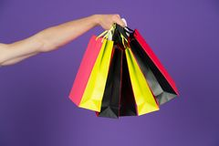 Shopping bags in hand on violet background. Paper bags of different colors. Bags or paperbags. Shopping or sale and black friday c Stock Photo