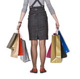 Shopping bags and legs. Lower body view of woman holding shopping bags isolated against a white background Stock Photo