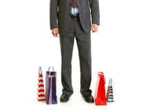 Shopping bags near businessman legs Royalty Free Stock Photography