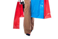 Shopping bags near legs in female hand Royalty Free Stock Image