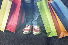 Shopping bags next to female feet. Shopping bags in various colors close to female feet Stock Images