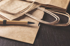 Shopping bags and pen on desk. Close up of brown shopping bag handles and pen placed on wooden desk Royalty Free Stock Image