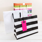 Shopping bags with pink tag. Shopping bags with pink sale tag on white wood table Stock Photography