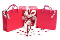 Shopping bags and present. A red present with shopping bags, on a white surface with stars Stock Photos