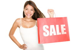 Shopping bags sale woman. Shopping sale woman showing shopping bag with sale written. Beautiful smiling asian woman showing red shopping bags. Mixed Chinese stock image