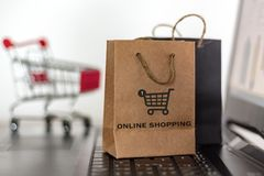 Shopping bags and trolley on laptop. Online shopping, e-commerce concept.  stock images
