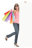 Shopping bags woman showing advertisement sign. Shopping woman showing commercial sign. Full length picture of a beautiful young mixed race woman holding a blank royalty free stock photos