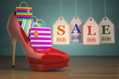 Shopping bags in women high heel shoes and labels sale. Concept Royalty Free Stock Image