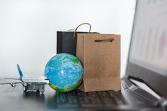 Shopping bags with world globe and airplane on laptop. Worldwide online shopping concept.  royalty free stock photo